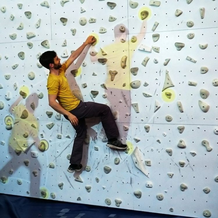 Climber on wall with his own videoimage.